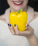 Woman holding a yellow pepper in her hand Stock Photo