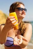 Woman is holding yellow tube with sunscreen tan Stock Photos