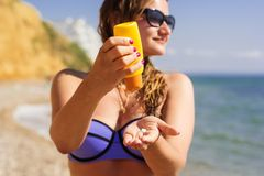 Woman is holding yellow tube with sunscreen tan Royalty Free Stock Images