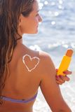 Woman is holding yellow tube with sunscreen tan Royalty Free Stock Image