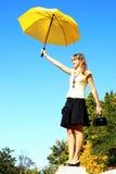 Woman holding a yellow umbrella. Beautiful woman holding in her hand a yellow umbrella Royalty Free Stock Images