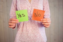 Woman holding yes and no cards. On wooden planks background Stock Photos