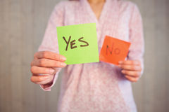 Woman holding yes and no cards. On wooden planks background Royalty Free Stock Photos
