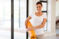 Woman holding yoga mat Stock Images