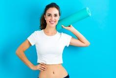 Woman holding yoga mat Stock Photos