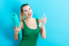 Woman holding yoga mat and water bottle Stock Image