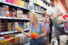 Woman holding yogurt from refrigerator. Positive women with family holding yogurt from refrigerator in hypermarket royalty free stock image