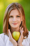 Woman holds apple. Young fine woman holds apple and smiles, on green background of summer city park Royalty Free Stock Images
