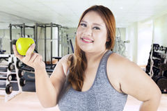 Woman holds an apple in the fitness center Stock Images