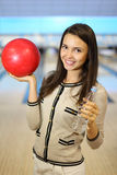 Woman holds ball and bottle in bowling club Royalty Free Stock Photo