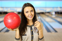 Woman holds ball and bottle in bowling club Royalty Free Stock Images