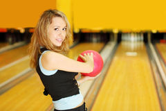 Woman holds ball and prepares to throw in bowling Stock Photos