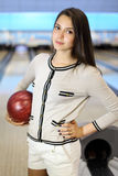 Woman holds ball and stands in bowling club Royalty Free Stock Photo