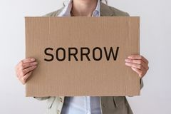 A woman holds a banner with the inscription SORROW. In front of her Royalty Free Stock Photo