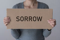 A woman holds a banner with the inscription SORROW. In front of her Stock Image