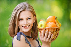 Woman holds basket with fruit. Young nice woman holds basket with fruit and pleasant smile, on green background of summer city park Stock Images
