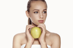 Woman holds big green apple in front of her face. Royalty Free Stock Photos