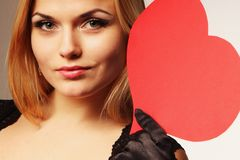 Beautiful woman holding artificial heart. Woman holds big red heart love symbol Royalty Free Stock Images