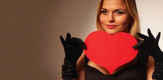 Beautiful woman holding artificial heart. Woman holds big red heart love symbol Stock Photos