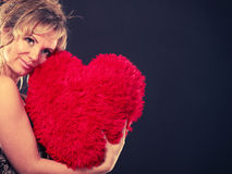 Woman holds big red heart love symbol. Woman mid age blonde female elegant evening dress holding big red heart love symbol studio shot on black. Valentines day royalty free stock photos