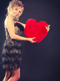 Woman holds big red heart love symbol. Woman mid age blonde female elegant evening dress holding big red heart love symbol studio shot on black. Valentines day royalty free stock image