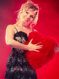 Woman holds big red heart love symbol. Woman mid age blonde female elegant evening dress holding big red heart love symbol studio shot on red. Valentines day royalty free stock photography