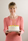 Woman holds birthday cake with lighted candles royalty free stock photography
