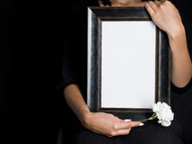 Woman holds blank mourning frame, with flower Royalty Free Stock Image
