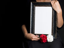 Woman holds blank mourning frame, with flower Stock Images
