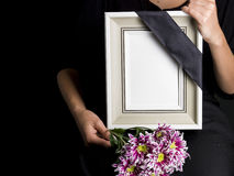 Woman holds blank mourning frame, with flower Stock Photo