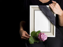 Woman holds blank mourning frame, with flower Royalty Free Stock Photos
