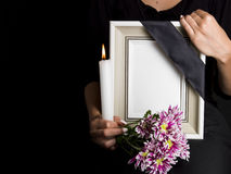 Woman holds blank mourning frame, with flower Royalty Free Stock Images