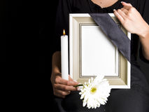 Woman holds blank mourning frame, with flower Stock Photography
