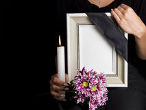 Woman holds blank mourning frame, with flower Royalty Free Stock Photo