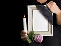 Woman holds blank mourning frame, with flower Royalty Free Stock Photography