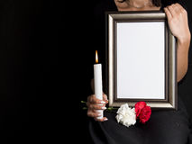 Woman holds blank mourning frame, with flower Stock Image