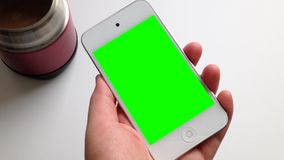 Woman holds a blank smart device with a green screen stock video footage