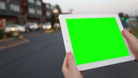 A woman holds a blank tablet PC with a green screen for your own custom content.