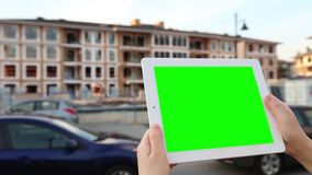 A woman holds a blank tablet PC with a green screen for your own custom content. stock footage