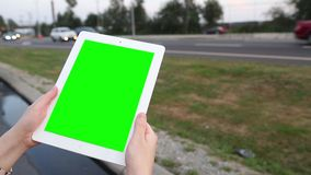 A woman holds a blank tablet PC with a green screen for your own custom content. stock video footage