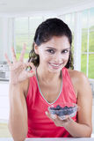 Woman holds blueberry fruit and show OK sign Royalty Free Stock Photos