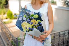 Woman holds a bouquet of callas, cornflowers and hydrangea Royalty Free Stock Image