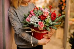 Woman holds a bouquet with fir branches, succulents, pink roses, red poppies. Woman in gray sweater holds a bouquet with fir branches, succulents, pink roses Stock Photo