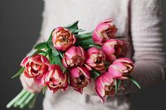 Woman holds a bouquet of spring pink tulips flowers. Vintage lifestyle scene with beautiful day light. stock photo