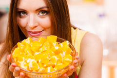 Woman holds bowl full of sliced orange fruits. Woman young housewife in kitchen holds bowl full of sliced orange fruits preparing to make fresh juice or salad Royalty Free Stock Photo