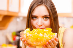 Woman holds bowl full of sliced orange fruits Royalty Free Stock Photo