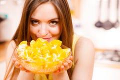 Woman holds bowl full of sliced orange fruits Royalty Free Stock Image