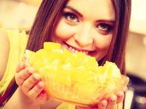Woman holds bowl full of sliced orange fruits Stock Images