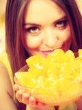 Woman holds bowl full of sliced orange fruits Stock Photo
