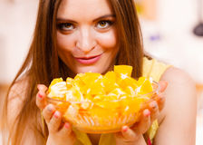 Woman holds bowl full of sliced orange fruits Royalty Free Stock Photography